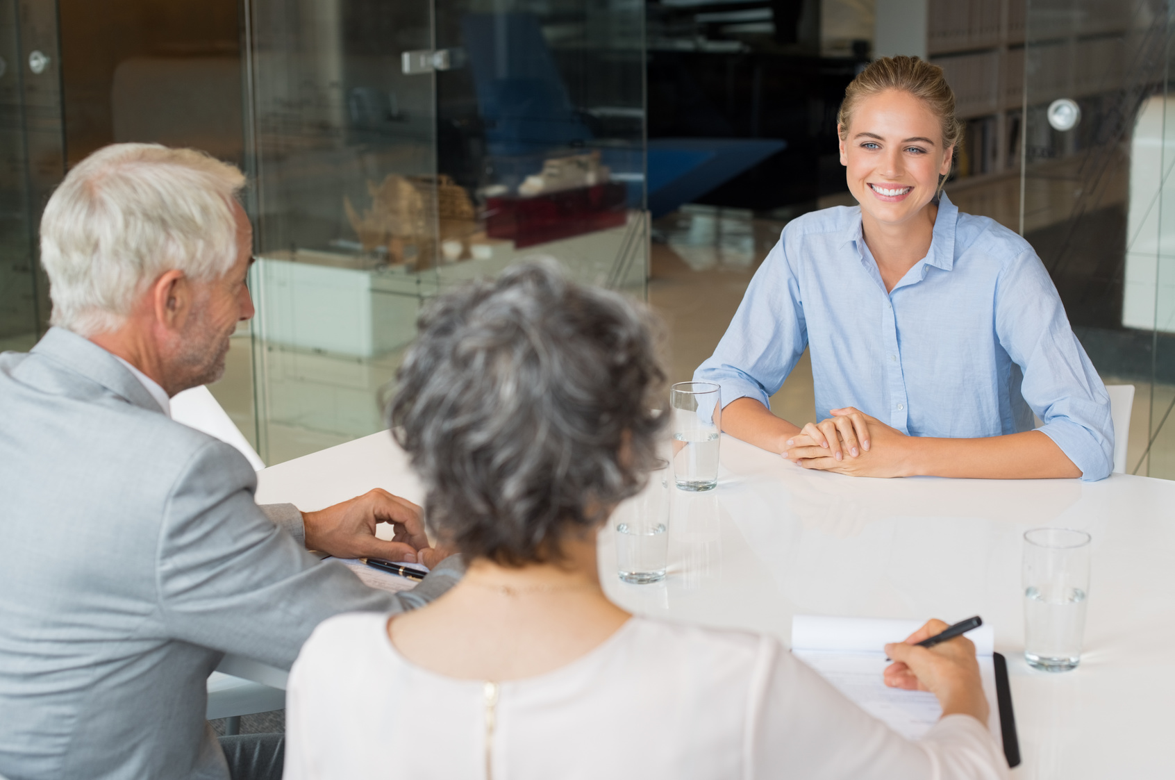 Woman in light blue polo during job interview smiling perfectly