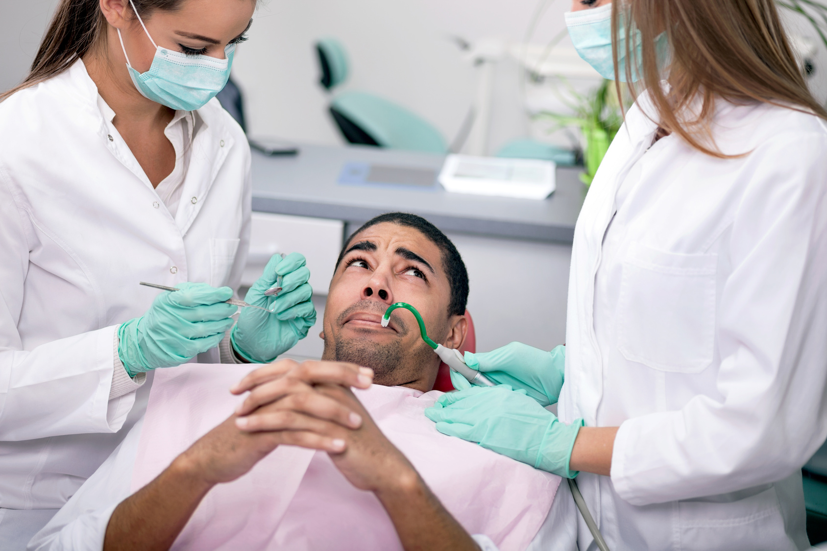 dentists trying to comfort nervous patient before a dental procedure