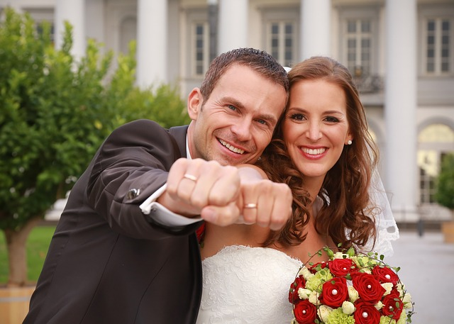 newly wed couple with showing off their wedding rings with a beautiful smile